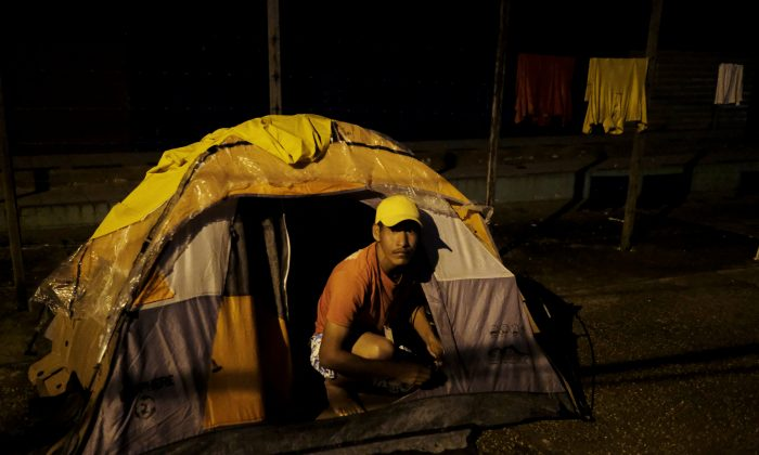 Venezuelan man is pictured at the entrance of his, tent set up along the street, as he waits to show his passport or identity card next day at the Pacaraima border control, Roraima state, Brazil August 8, 2018. Picture taken August 8, 2018. REUTERS/Nacho Doce