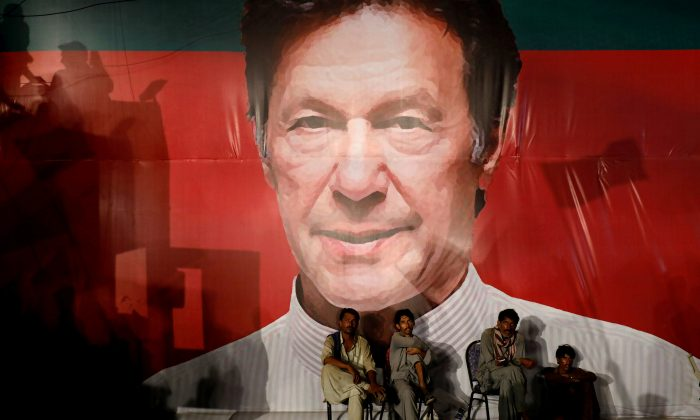 FILE PHOTO: Labourers, who set up the venue, sit under a wall with a billboard displaying a photo of Imran Khan, chairman of the Pakistan Tehreek-e-Insaf (PTI), political party, as they listen to him during a campaign rally ahead of general elections in Karachi, Pakistan July 22, 2018. REUTERS/Akhtar Soomro/File Photo