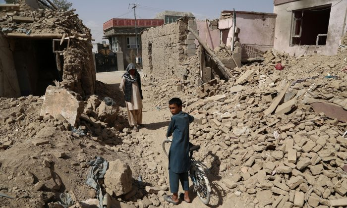 Afghan residents walk near destroyed houses after a Taliban attack in Ghazni on Aug. 16, 2018. (Zakeria Hashimi/AFP/Getty Images)