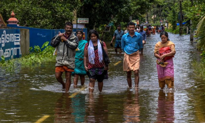 Locals cross foolded water on route to the Chengannur on 20/08/2018 in Kerala, India. Over 350 people have reportedly died in the southern Indian state of Kerala after weeks of monsoon rains which caused the worst flooding in nearly a century. Officials said more than 800,000 people have been displaced and taken shelter in around 4,000 relief camps across Kerala as the Indian armed forces step up efforts to rescue thousands of stranded people and get relief supplies to isolated areas.  Event Name: Floods Hit Southern Indian State of Kerala   Local Start Date: Monday, August 20, 2018   Local End Date: Saturday, August 25, 2018   Media Event ID: 775211625   City, Country:Kerala, India  Venue:  Event Notes:   Assigned Photographer(s): Atul Loke (Byline: Atul Loke, Byline Title: Stringer, Credit: Getty Images)
