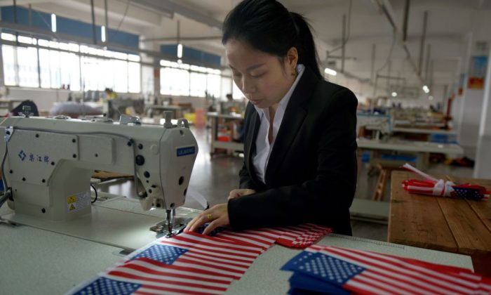 A Chinese employee makes US national flags at a factory in Wuyi, in China's eastern Zhejiang Province, on Nov. 6, 2017. (STR/AFP/Getty Images)