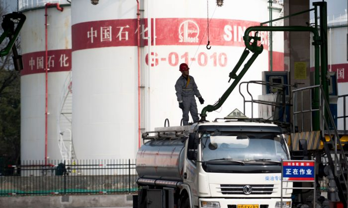 A man works at a filling station of Sinopec, China's state-owned oil company, in Shanghai, on March 22, 2018. (Johannes Eisele/AFP/Getty Images)