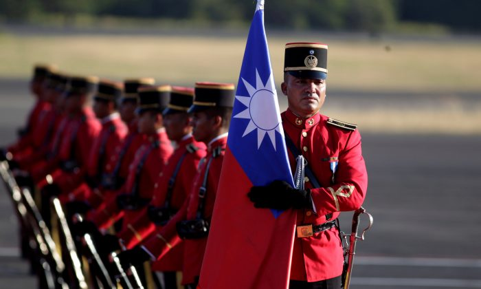 A honor guard holds a Taiwan flag before the arrival of Taiwan's President Tsai Ing-wen at the Oscar Arnulfo Romero International Airport in San Luis Talpa, El Salvador, on Jan. 12, 2017. (Jose Cabezas/Reuters)