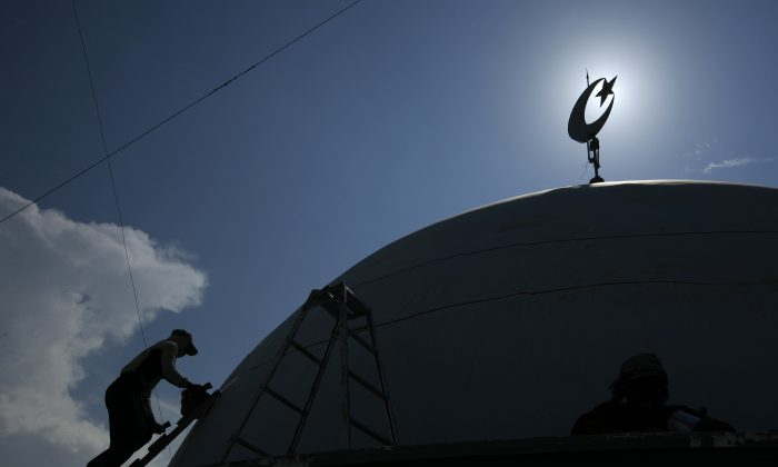 A worker paints the top of a mosque in Indonesia in a file photo. (Reuters/Beawiharta)
