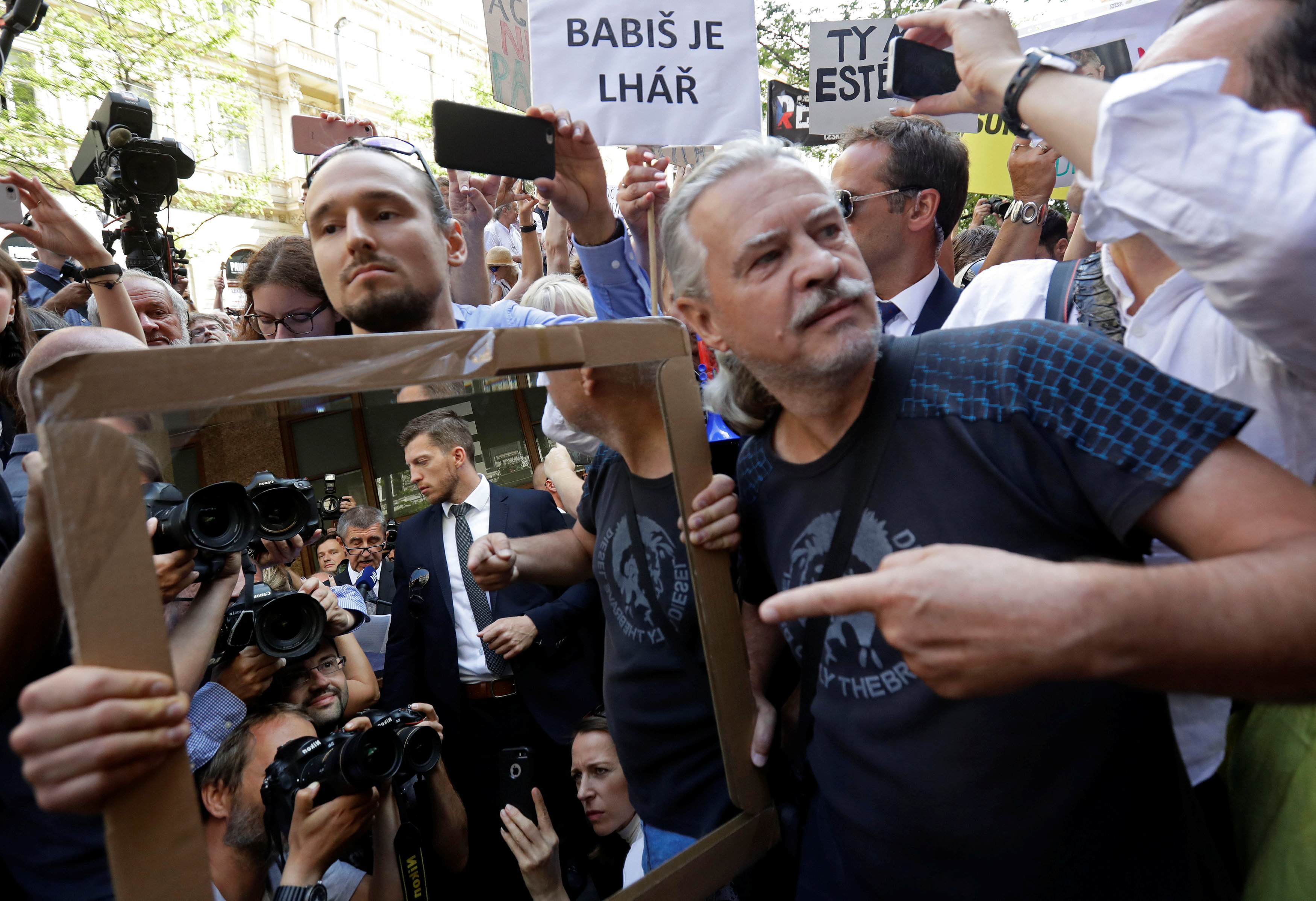 Demonstrators hold a mirror as they protest against Czech Prime Minister.