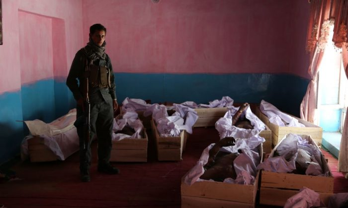 Afghan policeman stands next to the coffins containing corpses following clashes with Taliban fighters. (Zakeria Hashimi/AFP/Getty Images)
