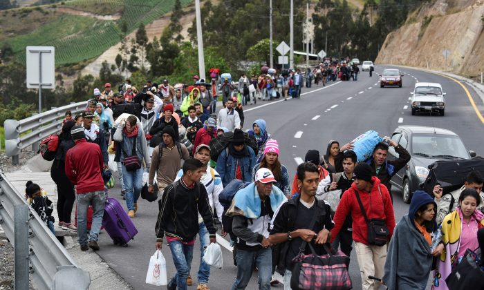 Venezuelan migrants heading to Peru walk along the Panamerican highway in Tulcan, Ecuador on Aug. 21, 2018. Ecuador announced on August 16 that Venezuelans entering the country would need to show passports from August 18 onwards, a document many are not carrying. (LUIS ROBAYO/AFP/Getty Images)