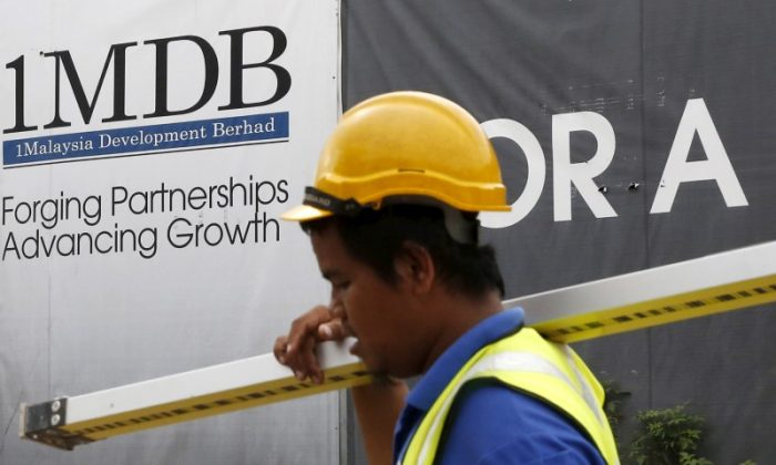 File Photo: A construction worker walks past a 1Malaysia Development Berhad (1MDB) billboard at the Tun Razak Exchange development in Kuala Lumpur, Malaysia February 3, 2016. (Reuters/Olivia Harris/File Photo)