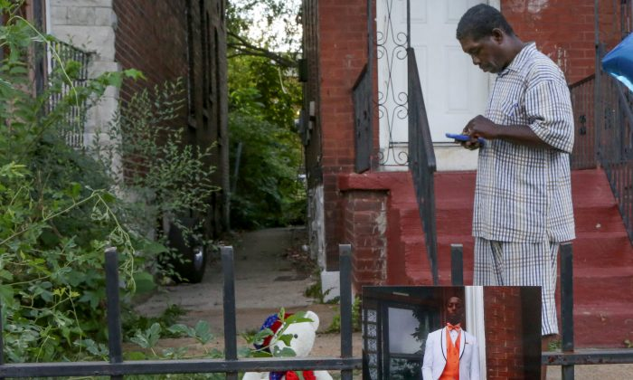 FILE PHOTO: Dennis Ball-Bey, the father of Mansur Ball-Bey, stands in front of the steps where police shot his son as a photo of Mansur hangs on the fence in St. Louis, Missouri, U.S., August 20, 2015.   REUTERS/Lawrence Bryant/File Photo