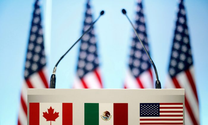 The flags of Canada, Mexico, and the United States on a lectern before a joint news conference on the closing of the seventh round of NAFTA talks in Mexico City, Mexico, March 5, 2018. (REUTERS/Edgard Garrido/File Photo)