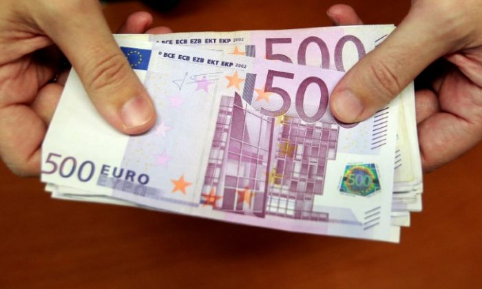 A bank employee holds a pile of 500 euro notes  at a bank branch in Madrid on Jan. 13, 2011. (Reuters/Andrea Comas)