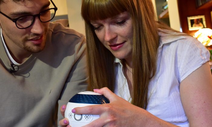 Designer Billy Searle shows his sister Jess how to use 'Mylo', a spherical games controller he has built to help people with disabilities to improve their mental fitness and dexterity in London, Britain on Aug. 9, 2018. (Reuters/Matthew Stock)