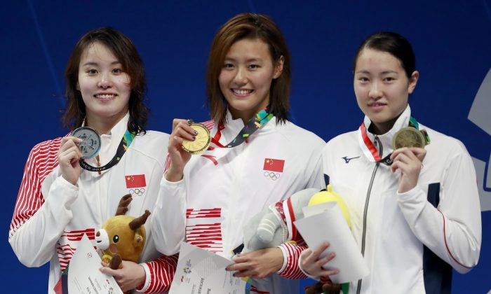 Women's 50m backstroke gold medalist China's Liu Xiang, centre, stands with silver medalist China's Fu Yuanhui, left, and bronze medalist Japan's Natsumi Sakai on the podium during the swimming competition at the 18th Asian Games in Jakarta, Indonesia on Aug. 21, 2018. (AP/Bernat Armangue)