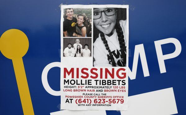 A poster for missing University of Iowa student Mollie Tibbetts hangs on the front door of a local business, Tuesday, Aug. 21, 2018, in Brooklyn, Iowa.