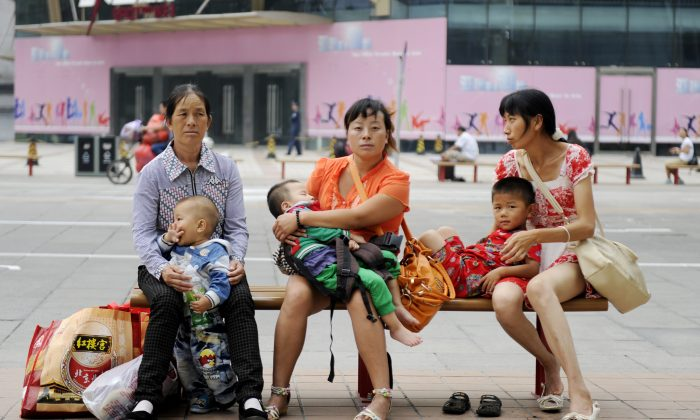 Women with their babies as they sit on a bench along a street in Beijing on September 6, 2012. (Wang Zhao/AFP/Getty Images)