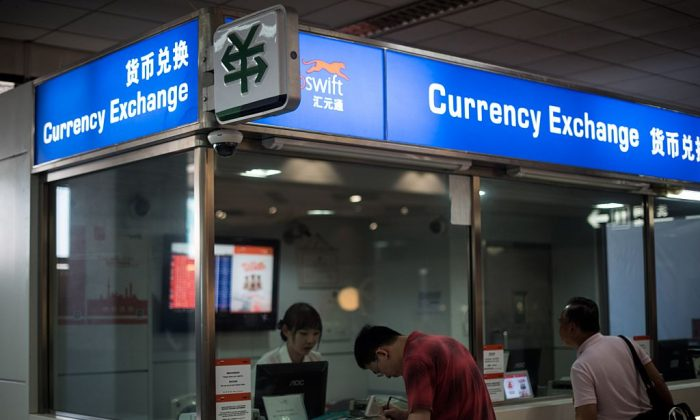 A man changes foreign currency into Chinese yuan at a currency exchange office in Hongqiao airport in Shanghai on August 14, 2015. (Johannes Eisele/AFP/Getty Images)
