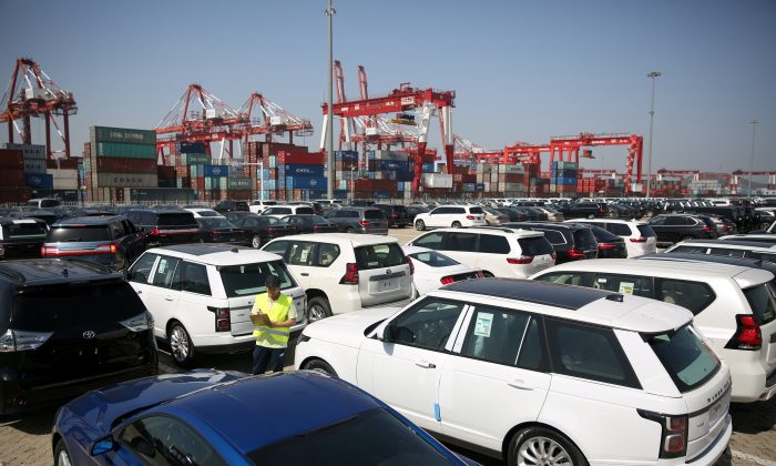 A worker inspects imported cars at a port in Qingdao City, Shandong Province, China, on May 23, 2018. (Stringer/Reuters)