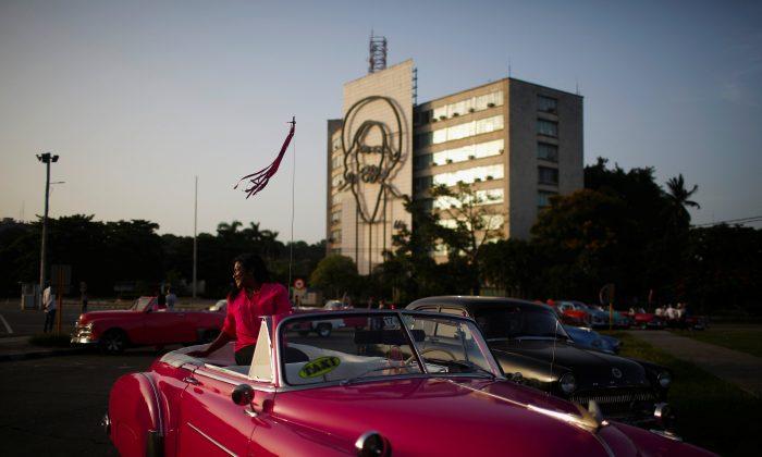 A tourist has a picture taken by a taxi driver in a vintage car at Plaza de la Revolucion in Havana, Cuba August 10, 2018. Picture taken August 10, 2018. REUTERS/Tomas Bravo