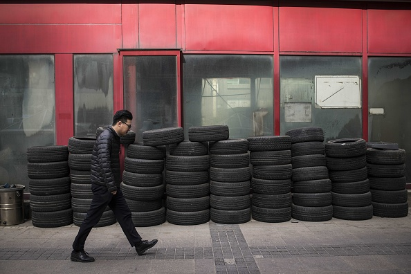 A man walks past used tyres in Beijing on February 9, 2018.