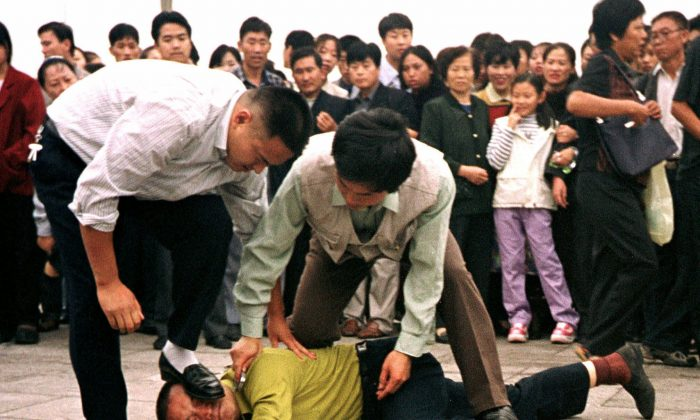 Police detain a Falun Gong adherent in Tiananmen Square, Beijing, on Oct. 1, 2000.  (AP Photo/Chien-min Chung)