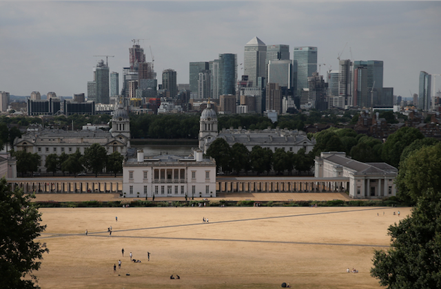 The financial offices of banks, including JPMorgan Chase, Citi, HSBC, and other institutions in the financial district of Canary Wharf, are pictured on the horizon as visitors to Greenwich Park walk and play on the dry brown grass in east London on July 23, 2018. (DANIEL LEAL-OLIVAS/AFP/Getty Images)