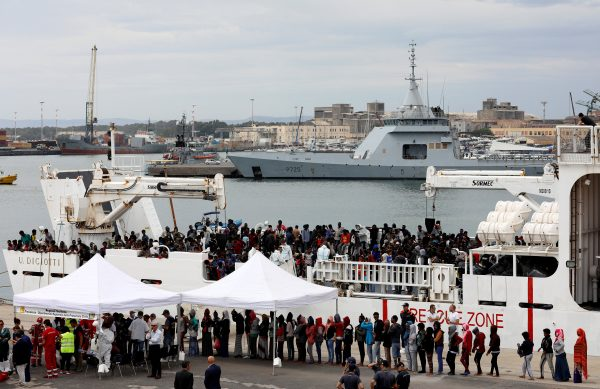 Migrants disembark from a coast guard vessel