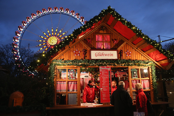 Visitors stop at a stall selling Gluehwein next to an illuminated ferris wheel at the Christmas market at Alexanderplatz on the market's opening day on Nov. 24, 2014 in Berlin, Germany. (Sean Gallup/Getty Images)