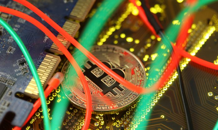 Representation of virtual currency bitcoin on a PC motherboard seen in this illustration picture, on Feb. 3, 2018. (Dado Ruvic/Reuters/Illustration).