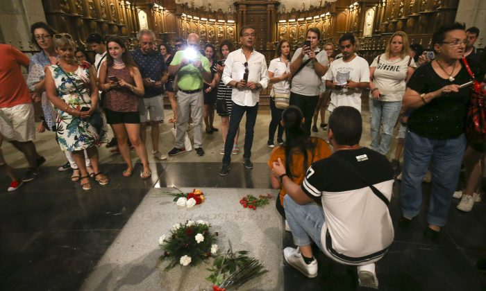 People stand around the tomb of former Spanish dictator Francisco Franco inside the basilica at the the Valley of the Fallen monument near El Escorial, outside Madrid on Aug. 24, 2018. (AP Photo/Andrea Comas)