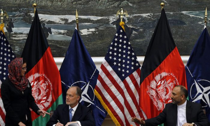 File Photo: Afghan national security advisor Hanif Atmar (R) and U.S. Ambassador James Cunningham sign the bilateral security agreement in Kabul September 30, 2014. (Reuters/Mohammad Ismail)