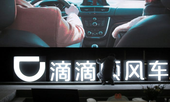 A man in front of a Didi Chuxing sign at a promotional event of its Hitch service, in Beijing on January 24, 2018. (REUTERS/Stringer/File Photo)