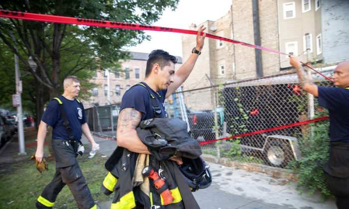 Chicago firefighters walk under tape at the scene of a fire that killed at least 8 people, including 6 children, in the 2200 block of South Sacramento Ave. on Aug. 26, 2018, in the Little Village neighborhood of Chicago. (Erin Hooley/Chicago Tribune)