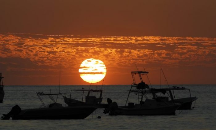 Boats are pictured during sunset at Herradura Beach in Punarenas, Jan. 8, 2015. (Reuters/Juan Carlos Ulate)