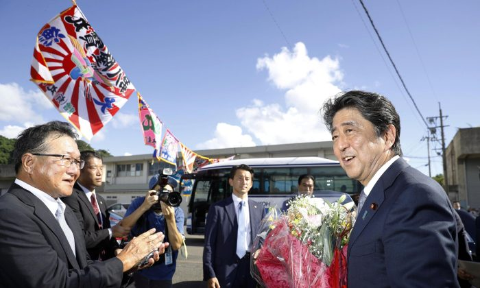 Japanese Prime Minister Shinzo Abe smiles as he receives a bouquet after announcing his candidacy for the ruling Liberal Democratic Party (LDP) leadership election in Tarumizu, Kagoshima Prefecture, Japan in this photo taken by Kyodo, August 26, 2018. Kyodo/via REUTERS