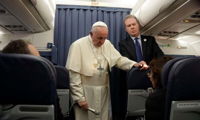 Pope Francis (C), flanked by Head of the Vatican press office, Greg Burke (R), addresses a reporter during a press conference in flight while returning from Ireland to The Vatican at the end of his two-day visit to Ireland on Aug. 26, 2018.  (GREGORIO BORGIA/AFP/Getty Images)