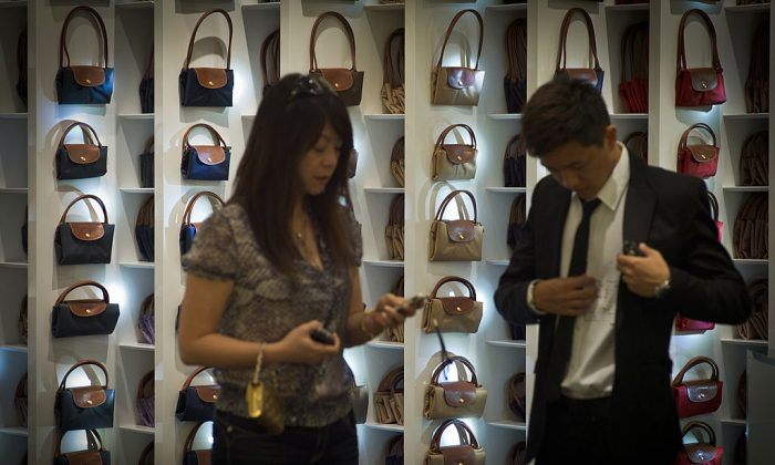 A man and a woman stand in front of handbags displayed at a store of luxury handbag maker Longchamp in Shanghai on Aug. 27, 2010. (Philippe Lopez/AFP/Getty Images)