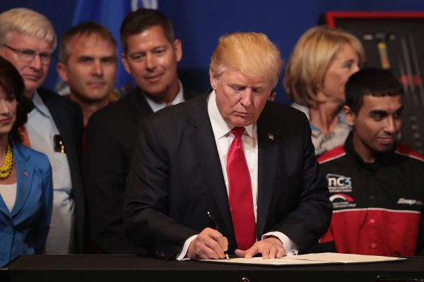 President Donald Trump signs an executive order to try to bring jobs back to American workers and revamp the H-1B visa guest worker program during a visit to the headquarters of tool manufacturer Snap-On in Kenosha, Wis., on April 18, 2017. (Scott Olson/Getty Images)