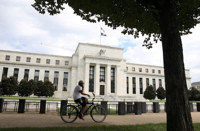 A cyclist passes the Federal Reserve building in Washington on Aug. 22, 2018. (Chris Wattie/Reuters)