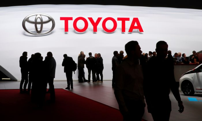 Visitors look at car models on the Toyota stand during the 88th Geneva International Motor Show in Geneva, Switzerland, March 7, 2018. (Reuters/Denis Balibouse).