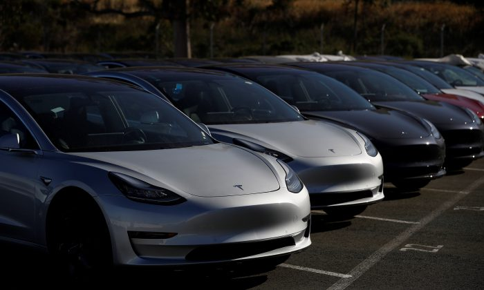 A row of new Tesla Model 3 electric vehicles is seen at a parking lot in Richmond, California, U.S. June 22, 2018. Picture taken June 22, 2018. (Reuters/Stephen Lam).