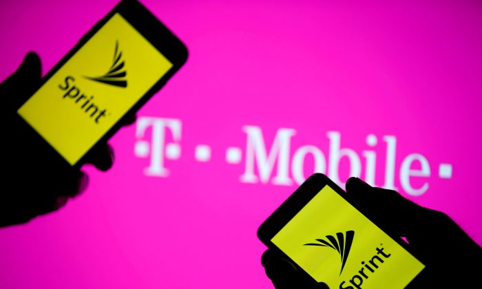 A smartphones with Sprint logo are seen in front of a screen projection of T-mobile logo, in this picture illustration taken April 30, 2018. (Reuters/Dado Ruvic/Illustration).