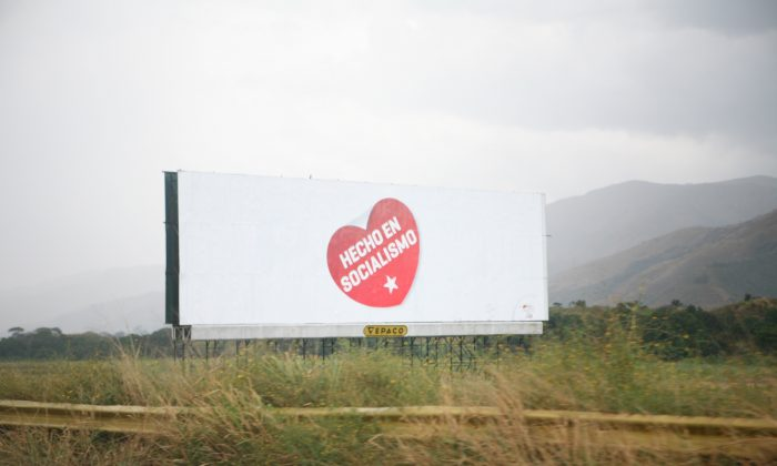 "A billboard in Venezuela promotes the slogan ""Made by Socialism"" in this file photo. The logo also features on confiscated products by private companies. (Creative Commons)"