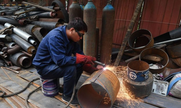 A man cuts a piece of steel pipe to make into a bracket at a workshop in Beijing on July 27, 2018. (Greg Baker/AFP/Getty Images)