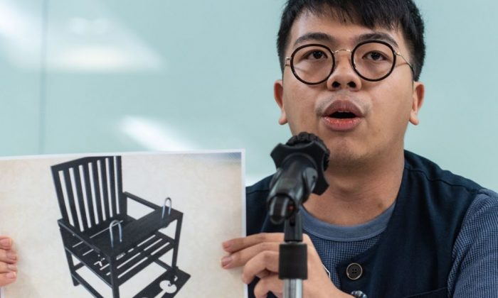"""Ivan Lam, chairman of pro-democracy group Demosisto, shows a picture of a """"prisoner's chair"""" to the media during a press conference in Hong Kong on Aug. 27, 2018. The group said Aug. 27 two of its members had been detained and questioned in mainland China. (Philip Fong/AFP/Getty Images)"""