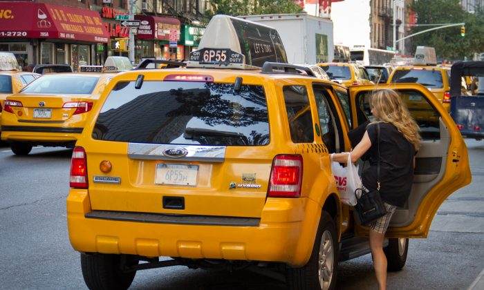 A women climbs into a taxi cab in New York City on July 12, 2012. (Benjamin Chasteen/The Epoch Times)