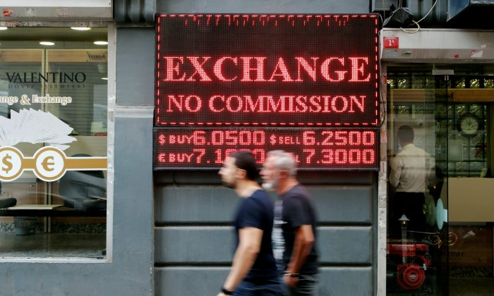 People walk past by a board showing the currency exchange rates next to a currency exchange office in Istanbul, Turkey August 28, 2018. REUTERS/Osman Orsal