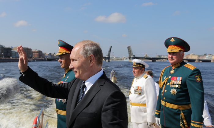 Russian President Vladimir Putin, Defence Minister Sergei Shoigu and Commander of Western military district Colonel-General Andrei Kartapolov attend the Navy Day parade in St. Petersburg, Russia July 29, 2018. (Sputnik/Mikhail Klementyev/Reuters)