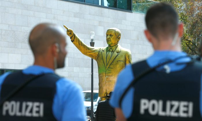 "Policemen stand in front of a statue of Turkish President Tayyip Erdogan during the art exhibition ""Wiesbaden Biennale"" in Wiesbaden, Germany, Aug. 28, 2018. (Reuters/Ralph Orlowski)"
