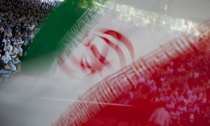 An Iranian flag flutters as worshippers attend Friday prayers in Tehran. (Reuters/Morteza Nikoubazl)