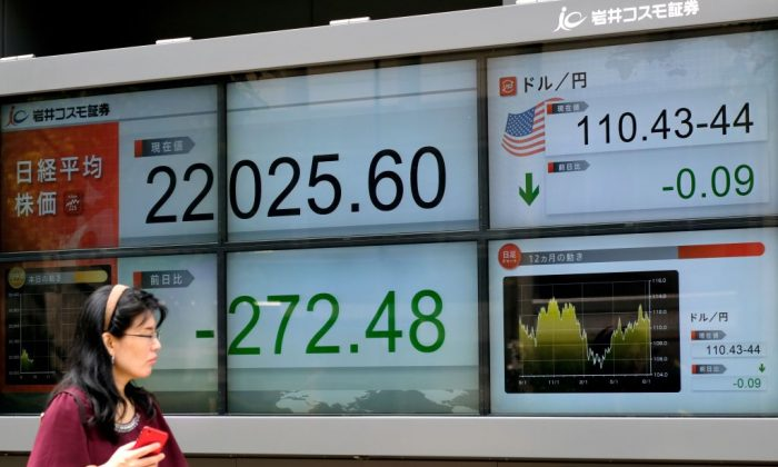 A pedestrian walks past an electronic board showing the share prices of the Tokyo Stock Exchange (L) and the foreign exchange rate between the yen and the US dollar (R) in Tokyo on Aug. 13, 2018. (Kazuhiro Nogi/AFP/Getty Images)